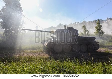 Soviet T-34-85 Tank In The Smoke On The Background Of The Church