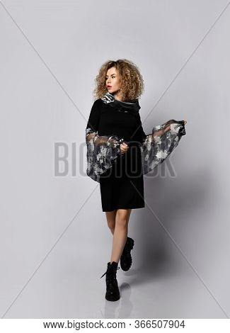 Young Beautiful Curly Woman In Stylish Black Dress And Massive Boots Walking Over Grey Wall Backgrou