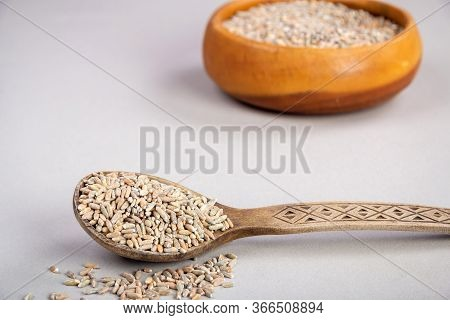 Unpeeled Raw Oats In A Wooden Spoon On A Wooden Table