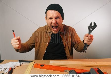 Portrait Of An Angry Scream Of A Screaming Male Locksmith Holding An Adjustable Wrench.