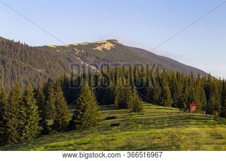 A Small Wooden Chapel On The Edge Of A Coniferous Forest In An Alpine Meadow Against The Background