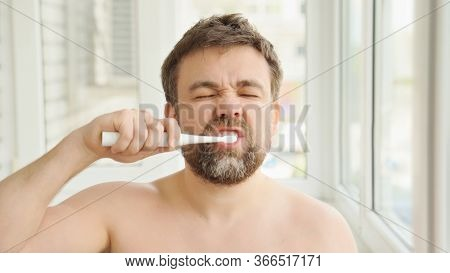 Sleepy Man With A Beard In The Morning Cleans The Teeth Electric Toothbrush. The Concept Of Daily Ca