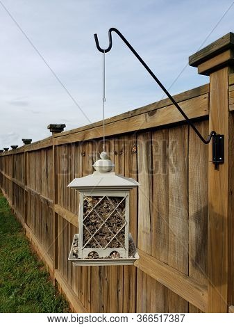 Bird Feeder Hanging from Fence at Residential Home