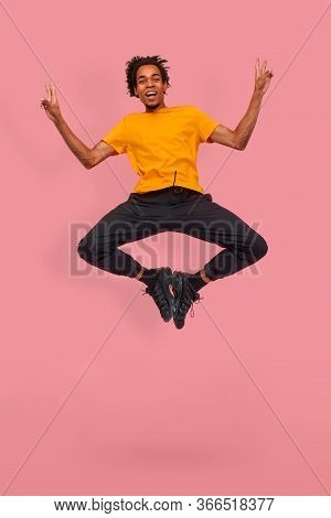 Full Length Shot Of Funny Young Dark Skinned Guy Jump In The Air In An Eccentric Pose On Pink Backgr