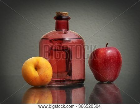 Still Life With Fruit Drink In The Vintage Glass Bottle, Juicy Ripe Peach And Red Apple Against A Lo