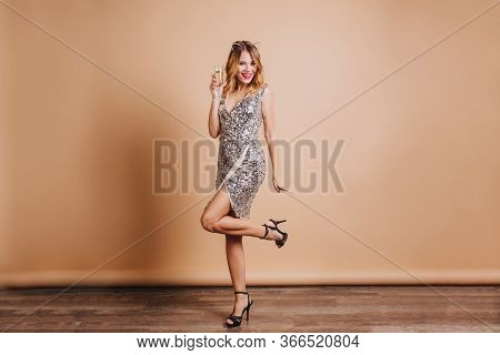 Full-length Portrait Of Happy Caucasian Female Model In Stylish Dress Standing On One Leg On Beige B