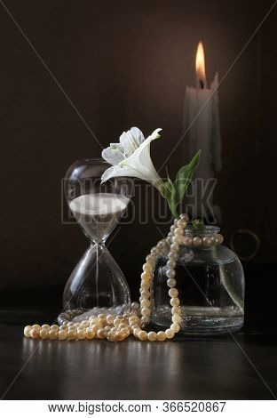 Retro Style Still Life With Alstroemeria Flower In The Small Bottle, Vintage Sandglass, Candlestick