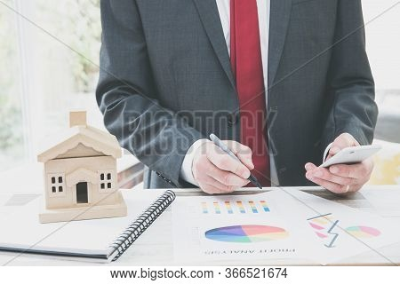 A Property Developer Or Real Estate Agent Working At His Desk And Calculating Or Analysing The Curre
