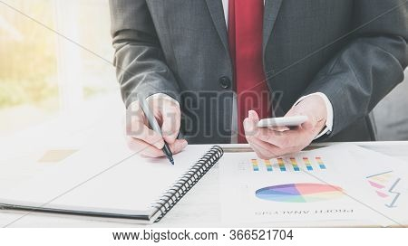 A Midsection Of A Businessman At His Desk Analysing And Calculating Business Costs And Accounting Wi