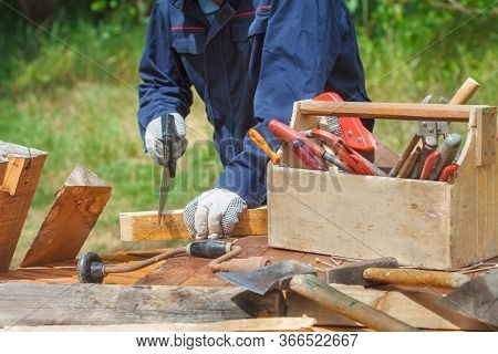 Wooden Toolbox With Different Vintage Worktools. Carpenter Sawing An Old Wooden Board.