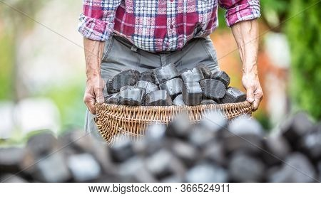 Detail Of Old Man's Arms Picking Up A Basket Full Of Coal Briquettes With A Blurred Pile Of Briquett