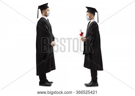 Full length profile shot of a university dean giving a diploma to a male graduate student and wearing protective face masks isolated on white background