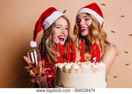 Good-humoured Female Models Laughing During Christmas Event. Inspired Girls Holding Wineglasses And