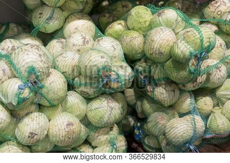 Old White Cabbage In Bags. Cabbage In Bags At The Market. The Vendors Use The Bamboo Strips To Make
