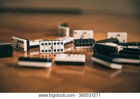 Domino Game Pieces On Brown Orange Wooden Floor Arranged Randomly