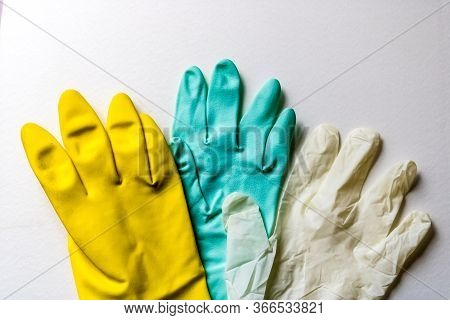 Green And Yellow Rubber Gloves And A White Latex Glove, Three Colorful Rubber Gloves - Image