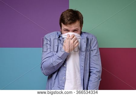 Man Feels A Fetid Odor, He Covered His Nose With A T-shirt, Squinted Eyes In Displeasure, And Squeez