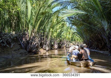 Asia, Vietnam, November, 2015 - Boat Travelers Sailing Along One Of The Tributaries Of The Mekong Ri