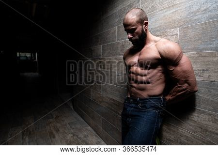 Model Standing Strong Against A Wall Posing