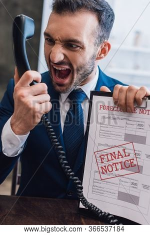 Aggressive Collector Shouting On Handset And Holding Documents With Foreclosure And Final Notice Let
