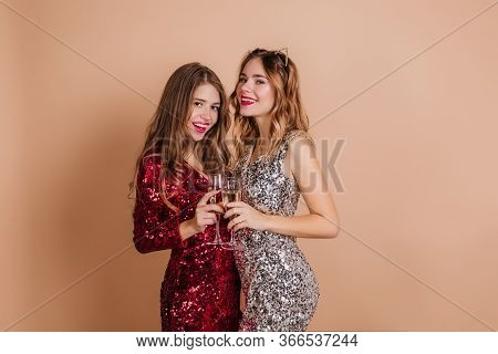 Dark-haired Woman With Long Hairstyle Gracefully Posing With Wineglass During Photoshoot With Friend