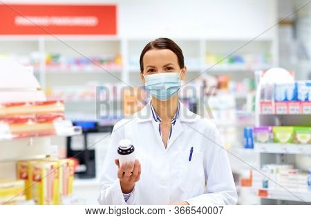 medicine, pharmaceutics and healthcare concept - happy female apothecary wearing face protective medical mask for protection from virus disease with drug at pharmacy