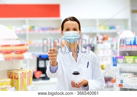 medicine, pharmaceutics and healthcare concept - happy female apothecary wearing face protective medical mask for protection from virus disease with drug showing thumbs up at pharmacy