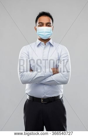 business, healthcare and people concept - indian businessman in shirt wearing face medical mask for protection from virus disease over grey background
