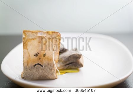 On A White Plate Are Used Tea Bags, A Used Tea Bag With A Drawn Sad Face.