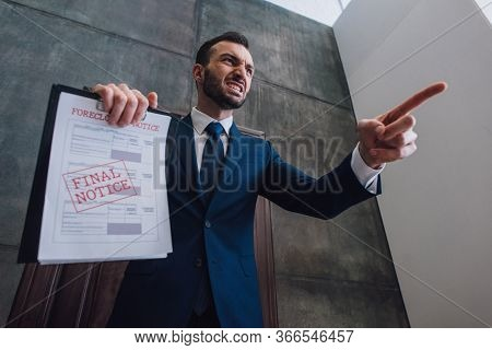 Low Angle View Of Angry Collector With Documents With Foreclosure And Final Notice Lettering Pointin