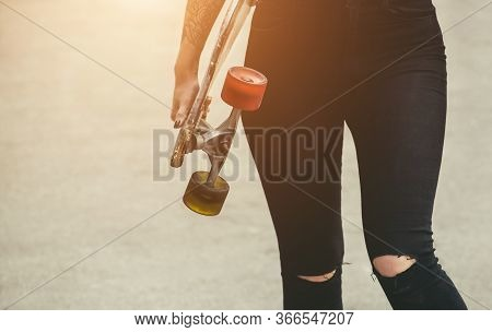 A Beautiful, Sexy Hipster Woman Stands With A Longboard  On The Street. Longboard Riding And Sport C