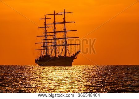A Red Burning Sunset With The Silhouette Of Sailing Ship. Sailors Set Sails On Masts Of Ship. White