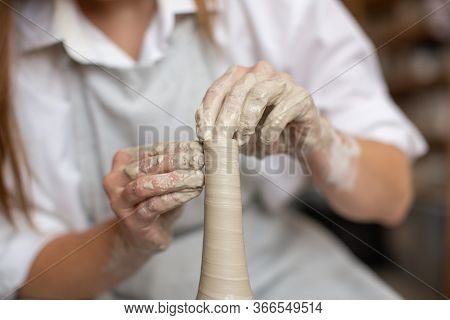 A Ceramist Woman Works On A Potters Wheel With Clay. The Breeding Of The Vase. Ceramic Workshop. Clo