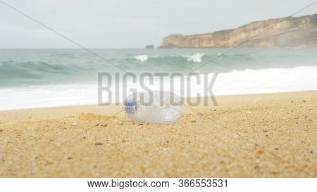 Plastic Bottle From Water Moves Along Yellow Beach By Strong Wind Against Rolling Ocean Waves Closeu