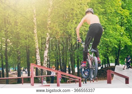 Teenager Does Stunts Jumping On A Bmx Stunt Bike On A Sunny Day In A City Park
