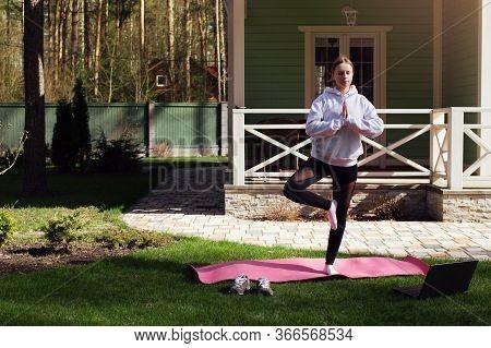 Woman Doing Sport Exercises, Yoga Meditation Vrikshasana Pose On Rug On Green Grass, With Online Tra