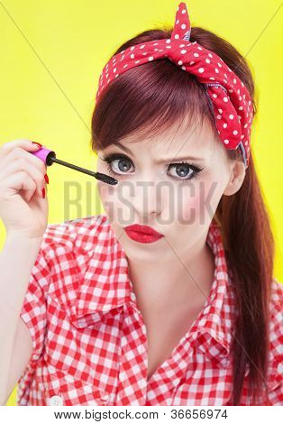 Funny portrait of girl applying mascara