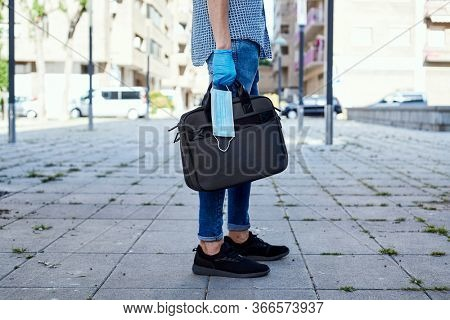 closeup of a young man, wearing blue latex gloves, carrying a briefcase and a surgical mask in his hand on the street
