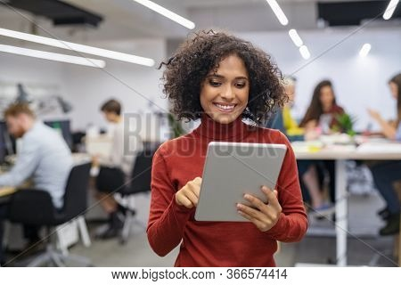 Happy multiethnic businesswoman with curly hair using digital tablet in office. Successful casual mixed race business woman working on laptop in workplace with colleagues sitting at desk in background
