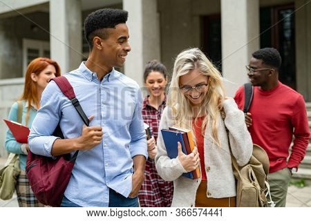 Happy smiling multiethnic friends walking outside college in conversation. Multiethnic group of university students feeling happy after study. Group of african young man and beautiful woman talking.
