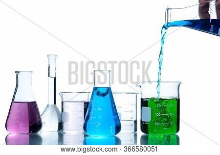 Scientist Put Blue Liquid Into Measuring Beaker  With Laboratory Glassware And Liquids Of Different