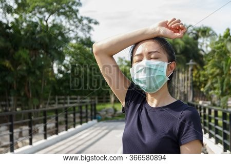 The Woman In Medical Protective Mask, She Tired From A Workout Rest. Female Athlete Suffering A Head
