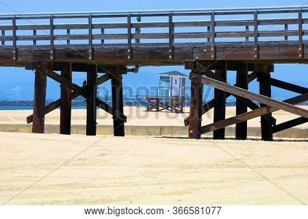 May 20, 2020 In Seal Beach, Ca:  Rustic Wooden Pier Above A Vast Sandy Beach With A Lifeguard Statio