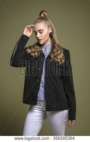 Outstanding Young Model Posing In Stylish Black Jean Coat And White Jeans. Olive Green Background.