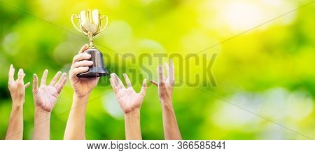 Many Hands Raised Up. Winner Is Holding Trophy Cup In Hand. On Blurred Green Background