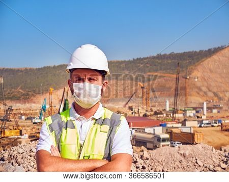 Builder In Medical Masl And Hardhat Stands Cross Handed Opposite Construction Site
