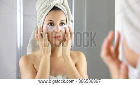 Beauty Woman Applying Anti-fatigue Under-eye Mask Looking Herself In The Mirror In Bathroom. Skin Ca