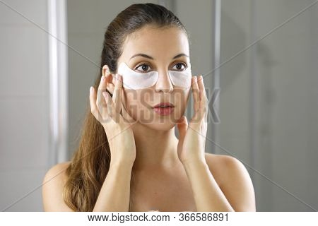 Beauty Woman Applying Under-eye Mask Looking Herself In The Mirror In The Bathroom. Skin Care Girl T