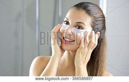 Smiling Beautiful Woman Applying Anti-fatigue Under-eye Mask Looking Herself In The Mirror In The Ba