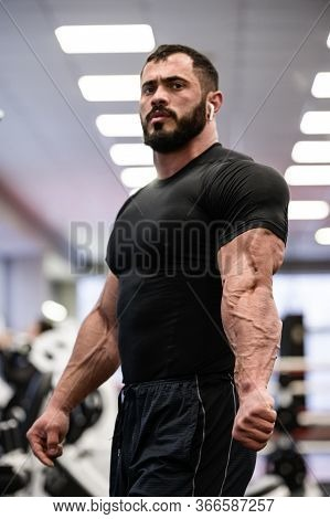 Strong Bearded Sport Young Man In Black Sportswear Showing His Muscle And Vein Separation On Triceps